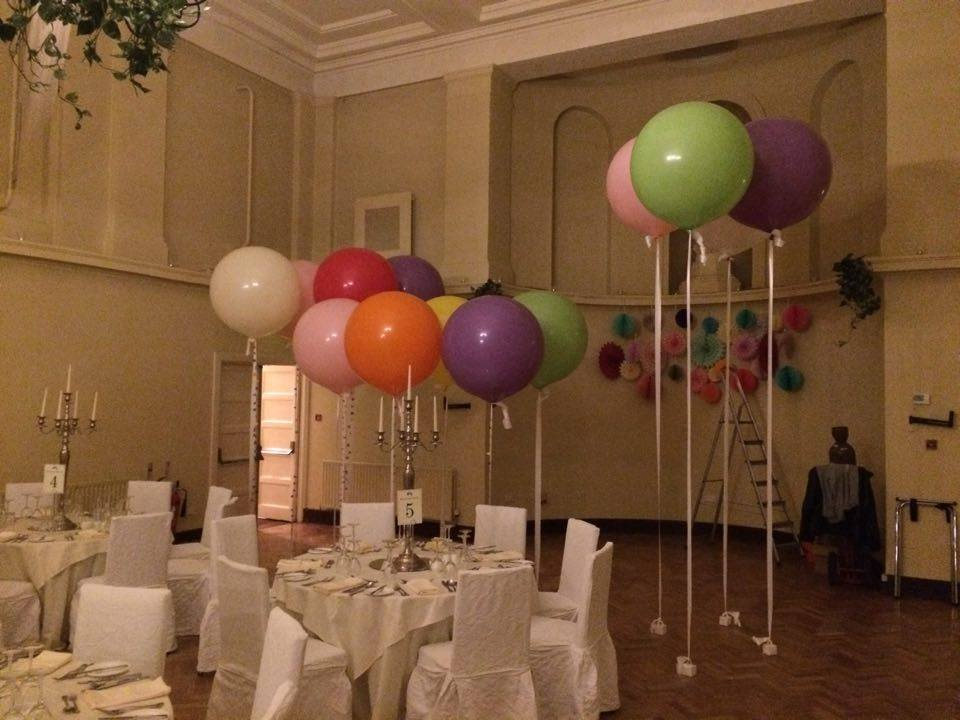 Different coloured large balloons floating from floor beside banquet table.