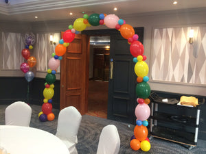 Large multicolour balloon arch over doorway  with balloon bouquet in corner of room.
