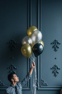 Man holding helium filled gold, silver and black balloons.
