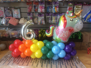 Multicolour balloon design with a unicorn balloon and silver number six balloon.