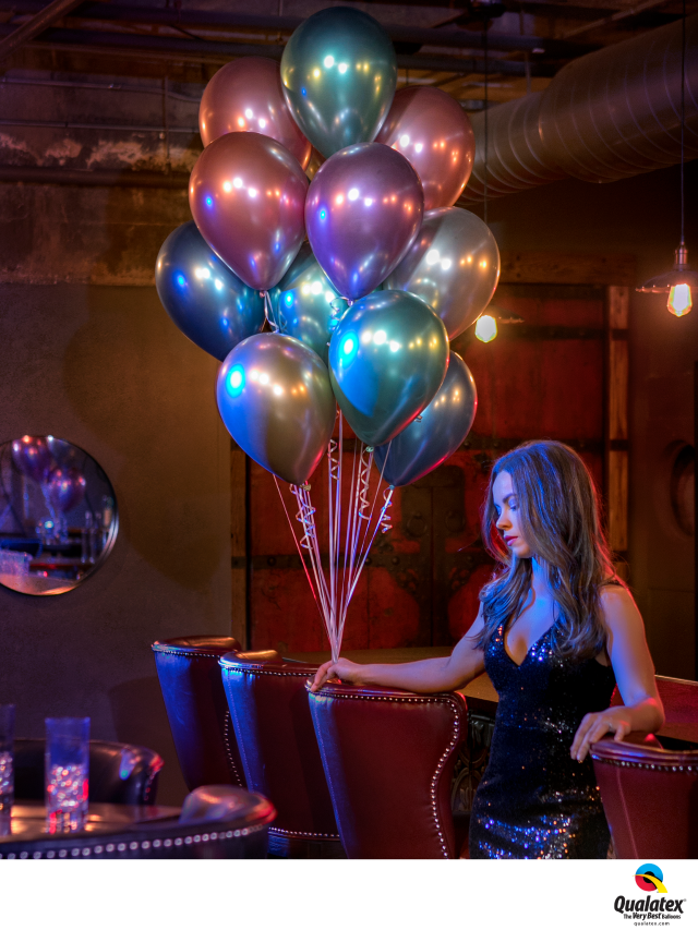 Girl holding bunch of shiny helium filled latex balloons.