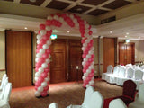Pink and white double balloon arch on metal stand.