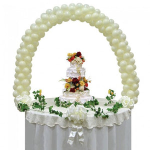 Ivory coloured balloon arch over a table.