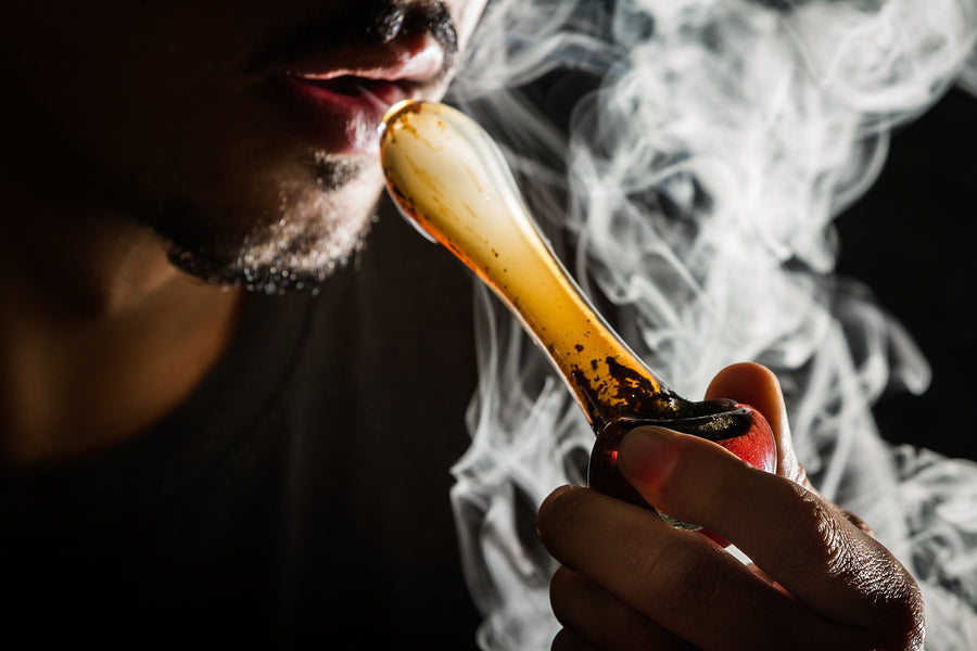 Image of a man smoking a glass pipe