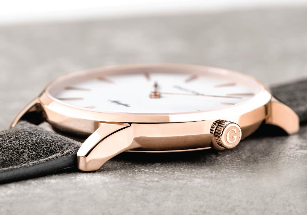 The Gallivant Aquafino watch with rose gold case and charcoal strap lying on a stone surface