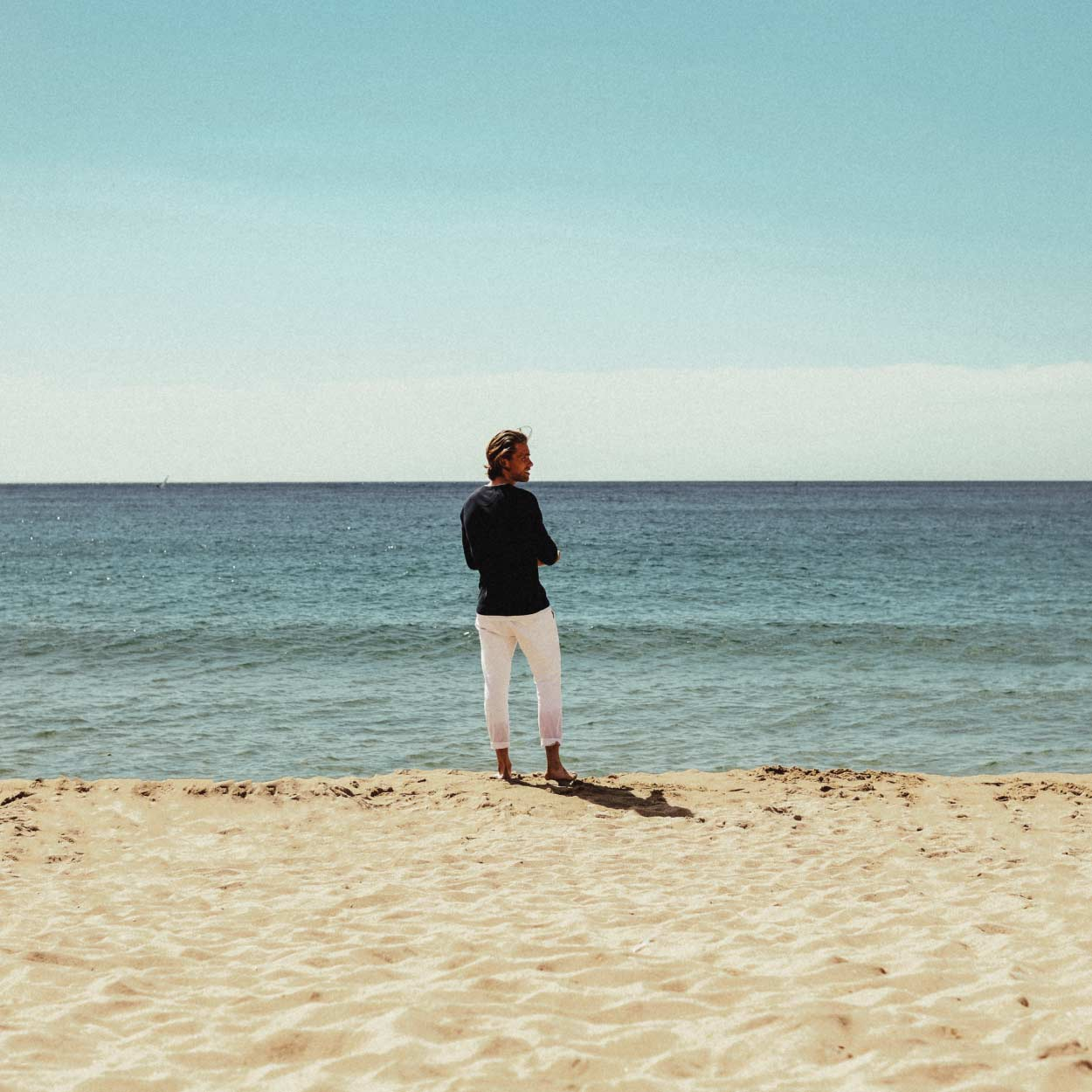Manin blue shirt and white pants standing on the beach looking to the side