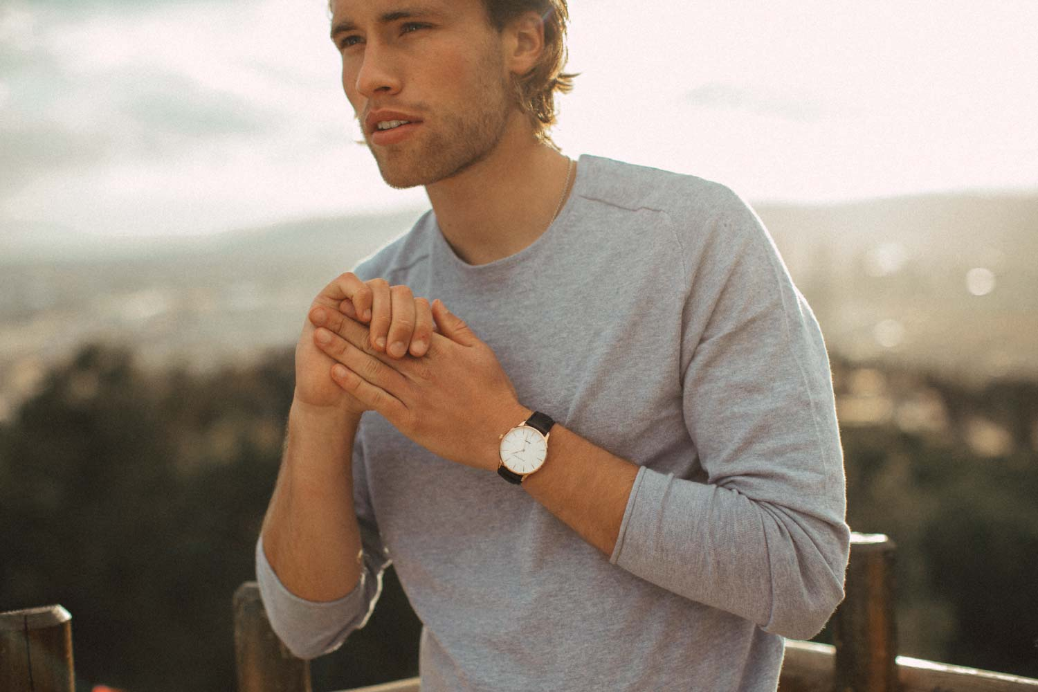 Man in grey shirt wearing the rose gold Aquafino watch with black strap