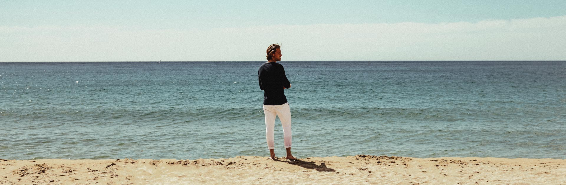 Man in blue shirt and white pants standing on the beach looking to the side