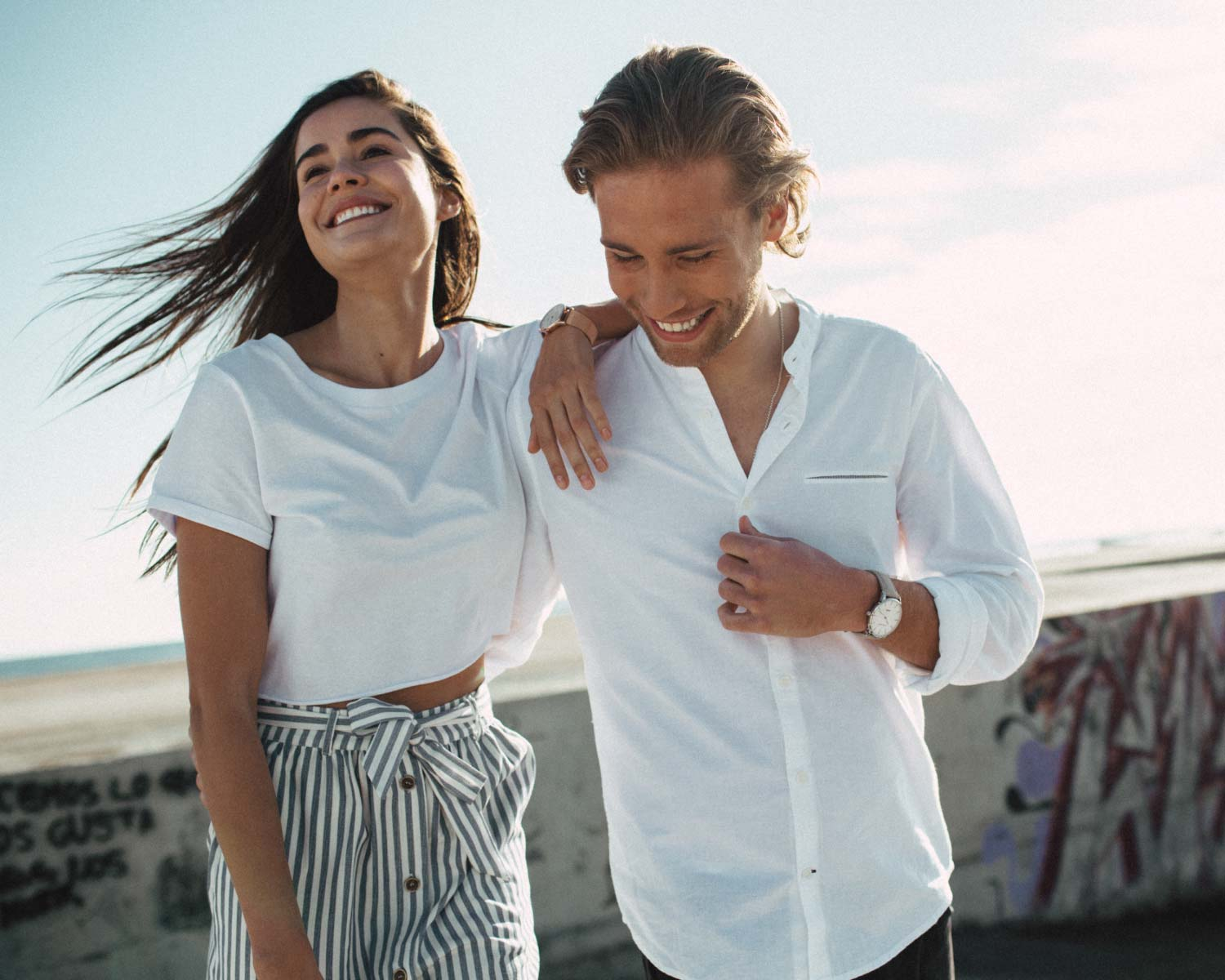 Couple with summer clothes wearing Gallivant Aquafino watches and having fun together
