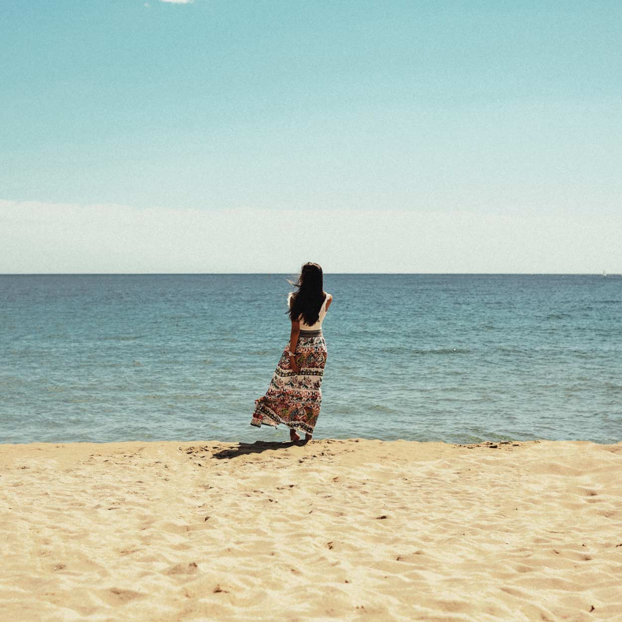 Woman in colorful dress standing on the beach looking at the horizon