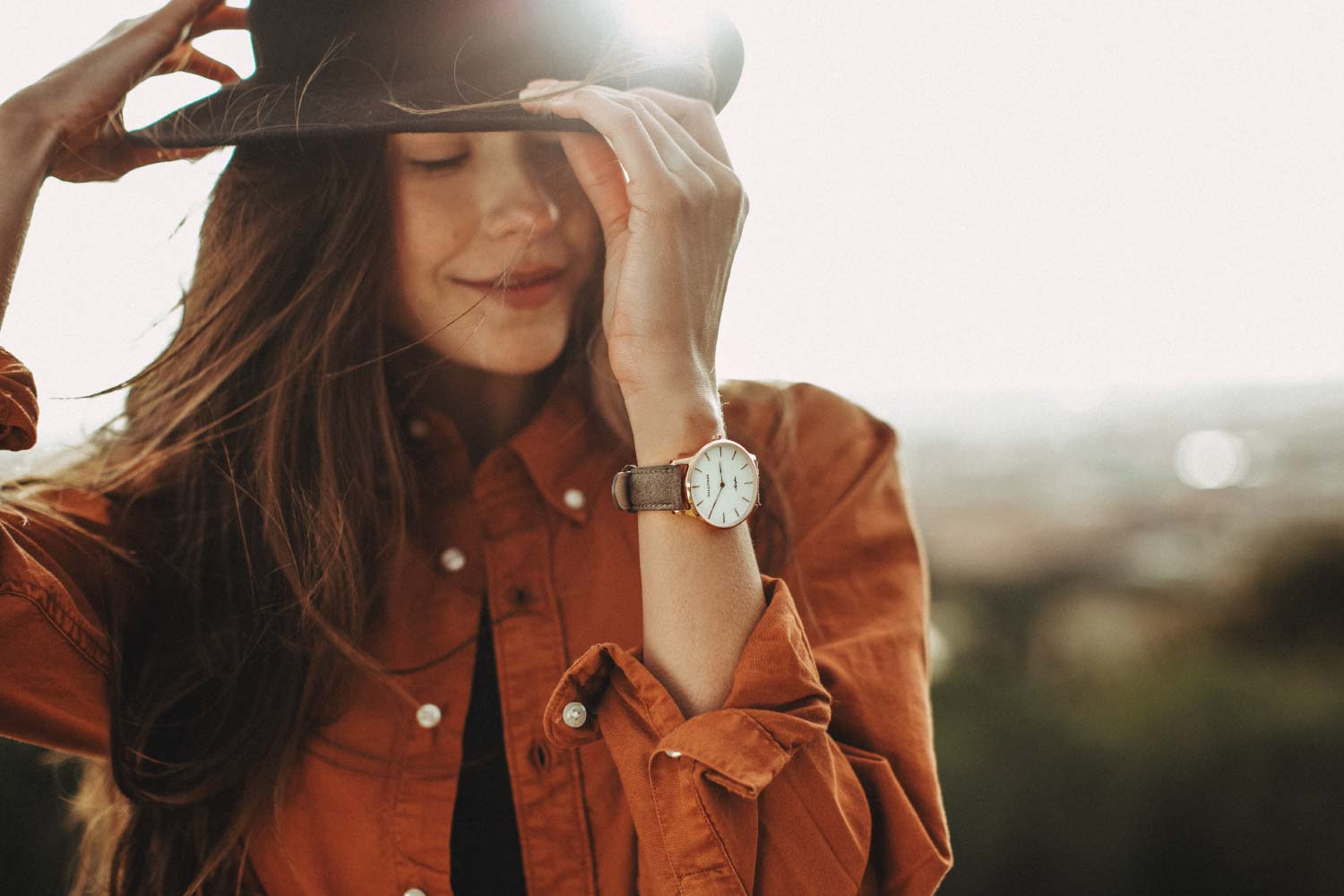 Woman with black hat and orange jacket wearing the rose gold Aquafino watch with charcoal strap