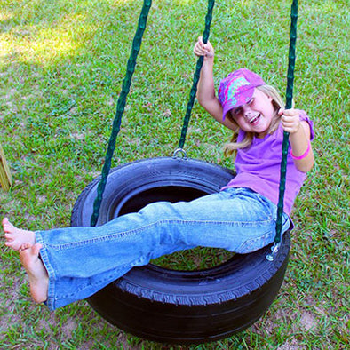 Child playing on Deluxe 3-Chain Tire Swing - black color