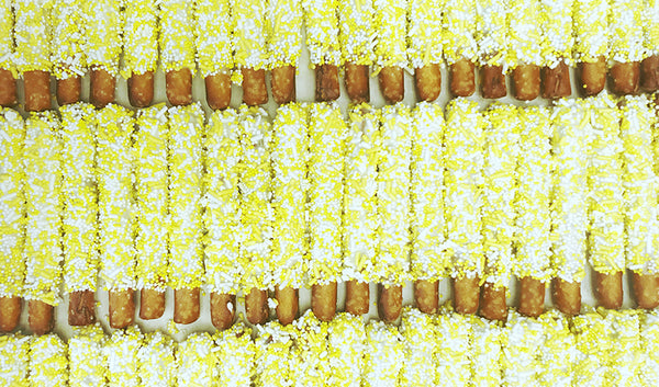 Chocolate covered pretzel rods with yellow and white sprinkles