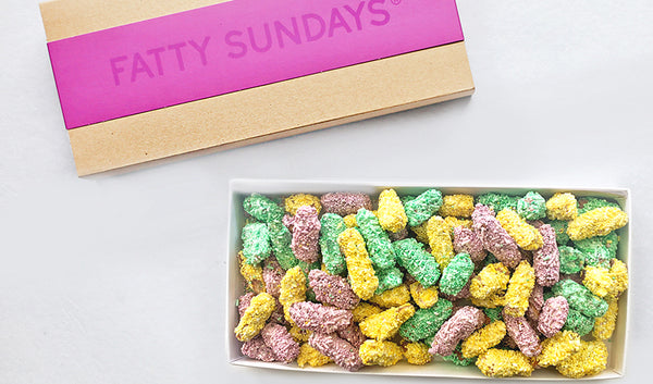 Easter gift box filled with chopped chocolate covered pretzels topped with pastel colored sprinkles