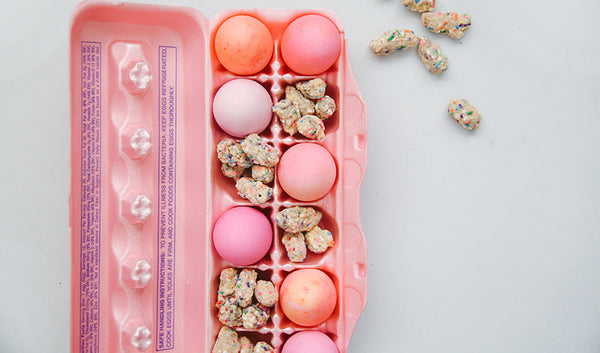 Pastel colored Easter eggs and chocolate covered pretzel bites in an egg carton