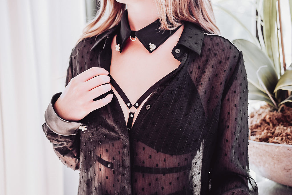 Sheer black blouse strappy bra satin cuffs collar gold lead