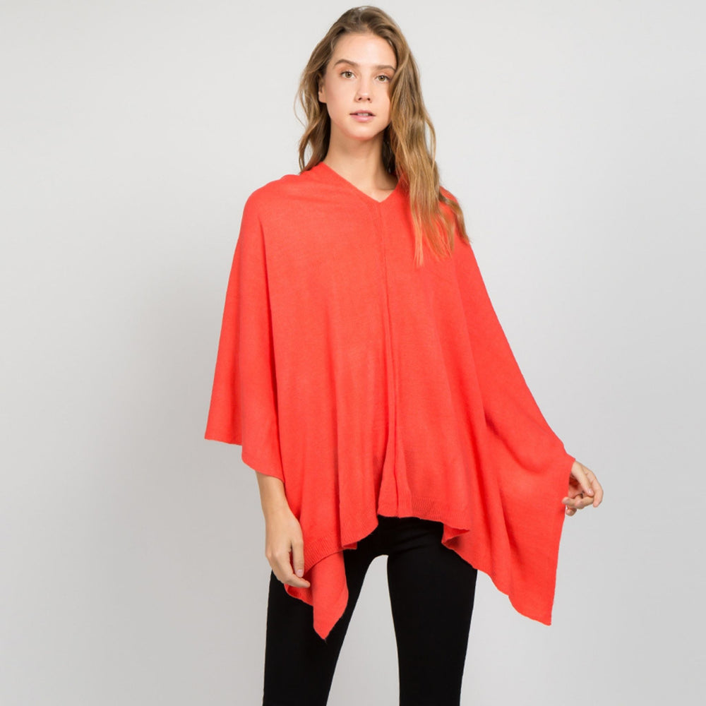 Young standing woman facing front wearing a coral colored poncho