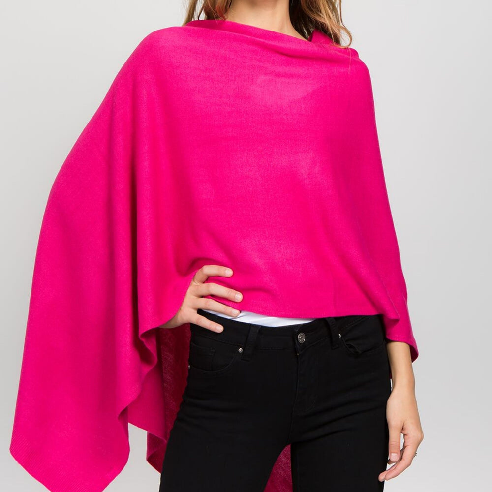 Young woman standing with hand on hip wearing a fuchsia poncho