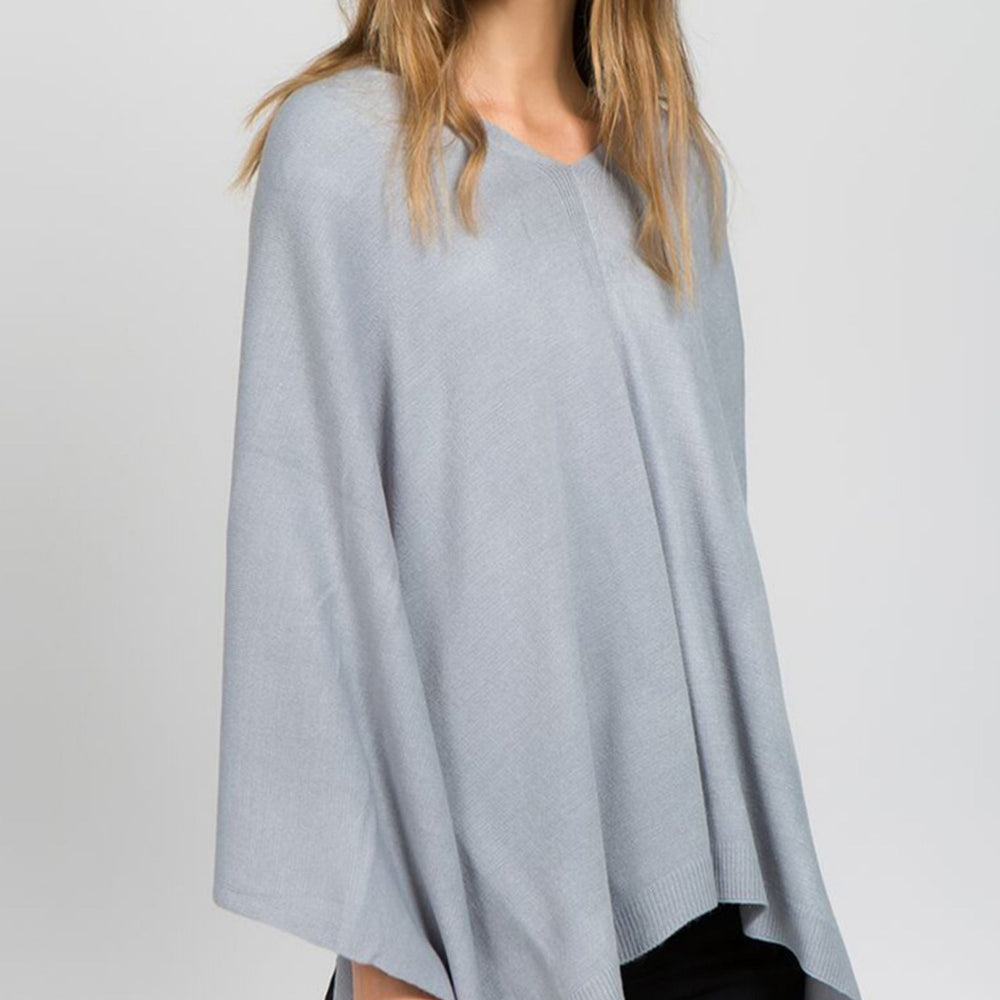Young woman standing and posing wearing a light grey poncho