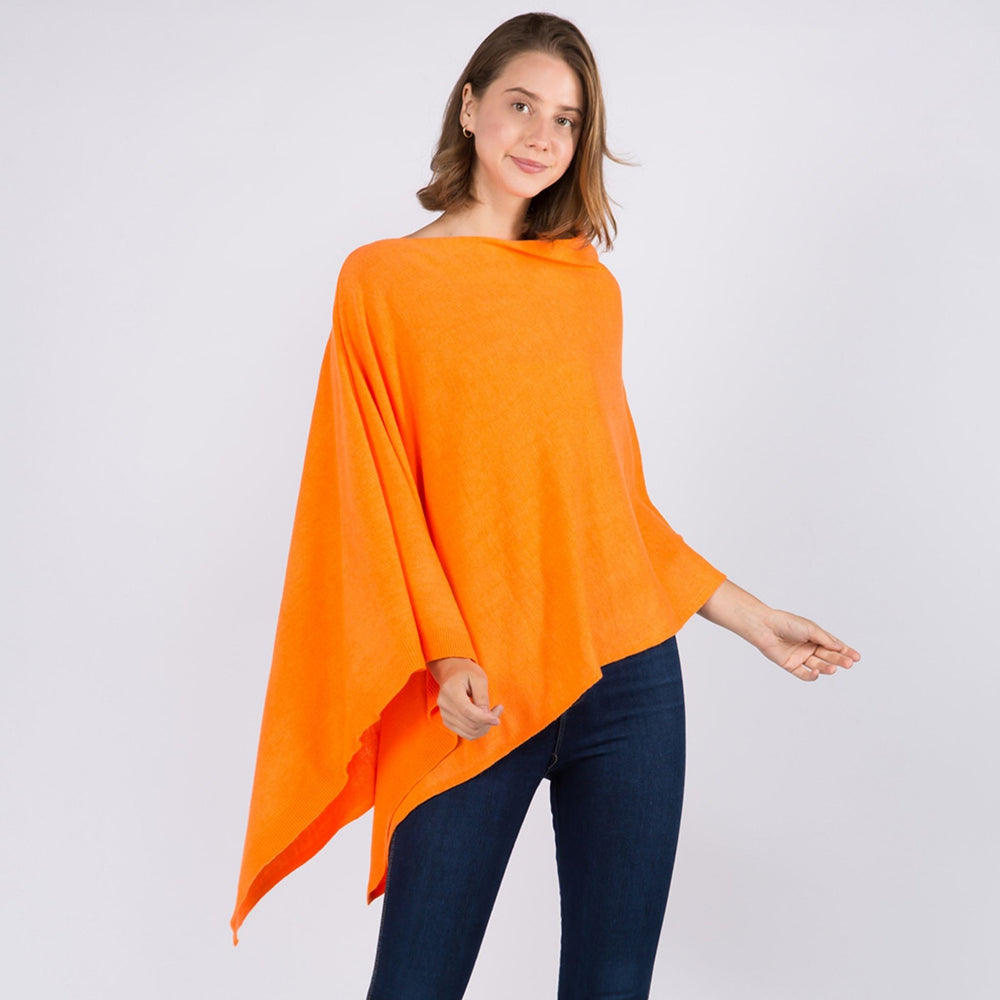 Young woman standing and posing wearing a neon orange colored poncho