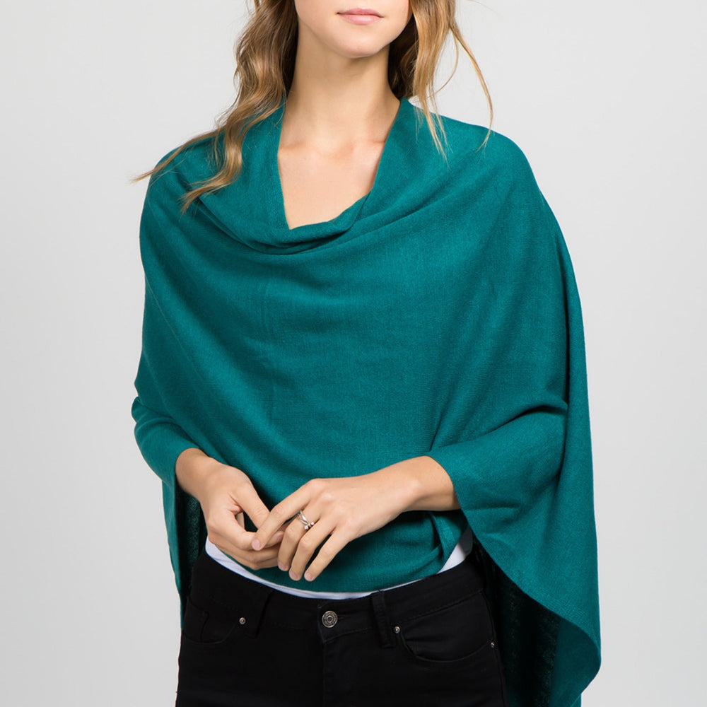 Young standing woman facing front with arms around waist wearing a teal poncho