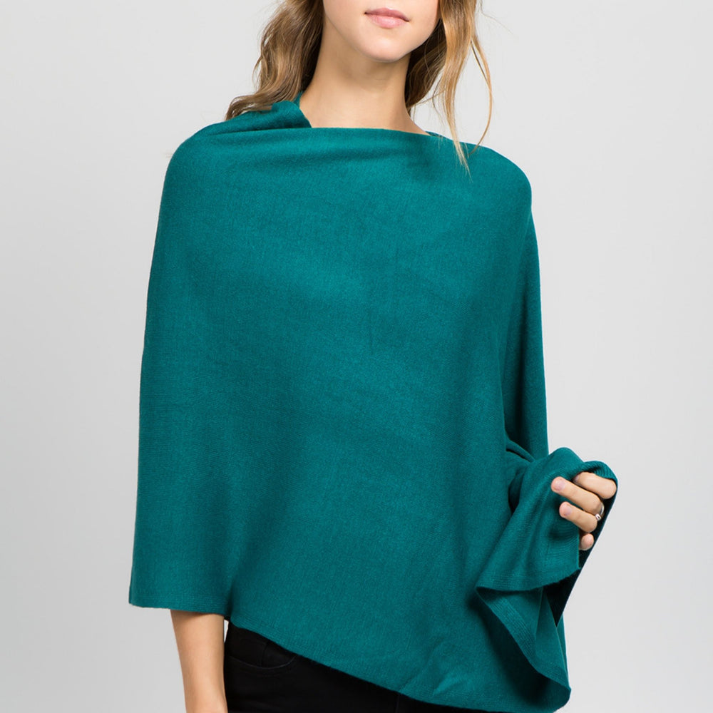 Young standing woman facing front wearing a teal poncho