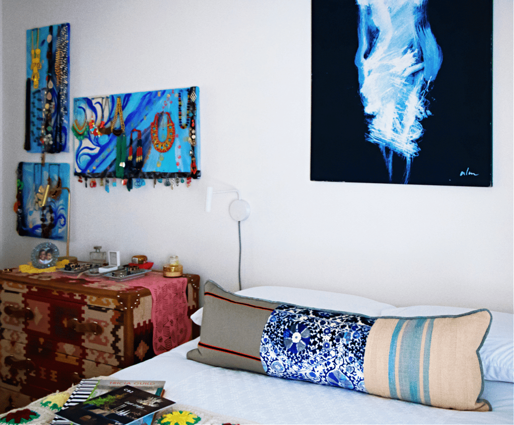 blue bedroom with lumbar pillow jewelry on the wall