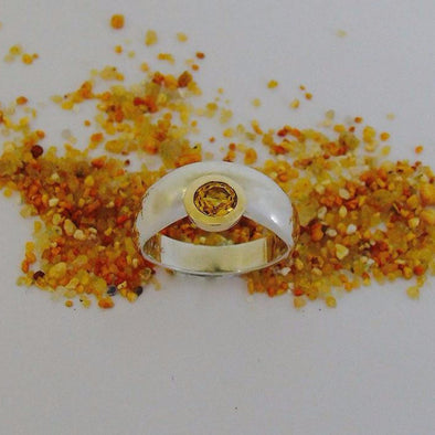 Sterling silver, set with a 5mm round faceted cut citrine in a 9ct yellow gold bezel setting.