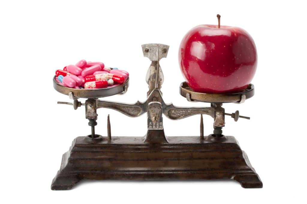medicine and an apple on the scales isolated on white background