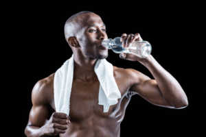 Athlete with towel around neck drinking water while standing against black background