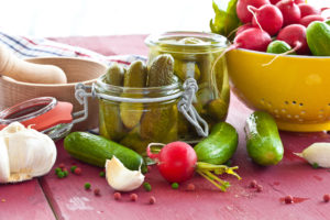 Pickling gherkins with spices and vinegar in vintage jars