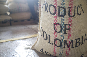 burlap sack of fresh green Colombian coffee beans