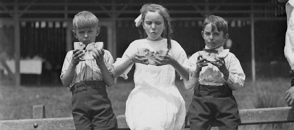Vintage image of children eating watermelon as a header for Faire Child's food blog.