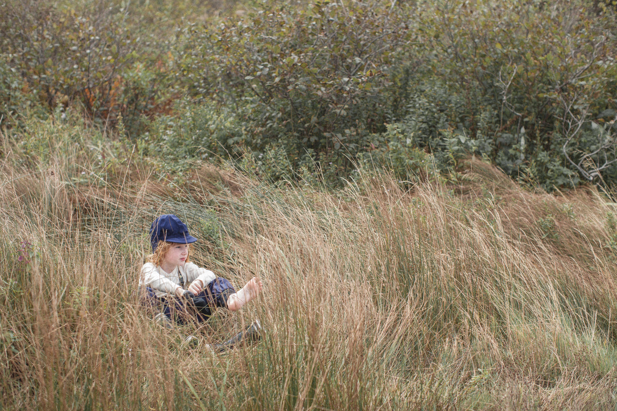 Child hiding in the grass while attending The Evergreen Club Forrest School.