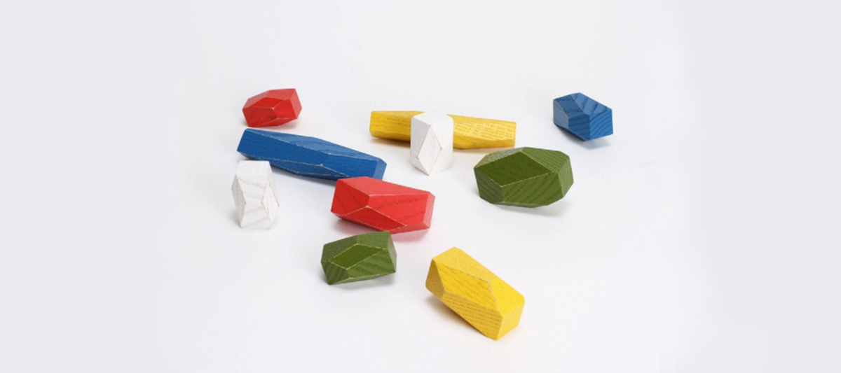 Picture of wooden blocks of different shapes and colours show what loose parts play is.