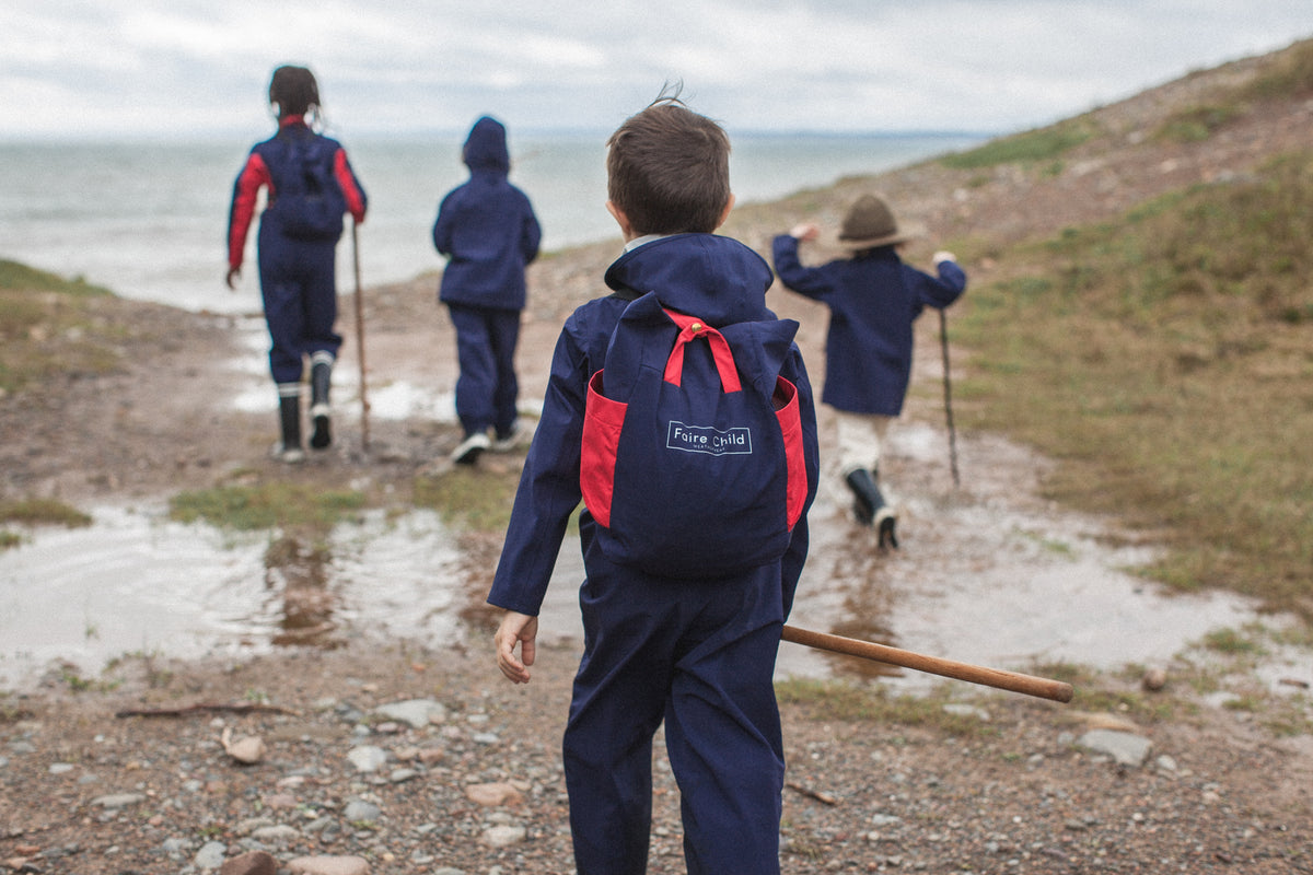 Children hiking towards water wearing eco friendly clothing by Faire Child.