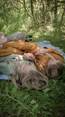 Girls wearing lightweight rain jackets while laying in the grass