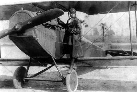 Bessie Coleman standing on the wing of her plane.