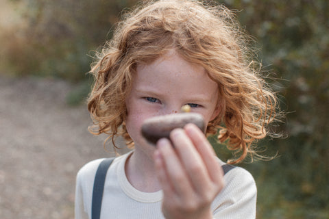 Child holding snail up to the camera during an afternoon at the forrest school.