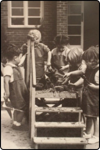Image of the the students at the open-air nursery playing outside in the mud.