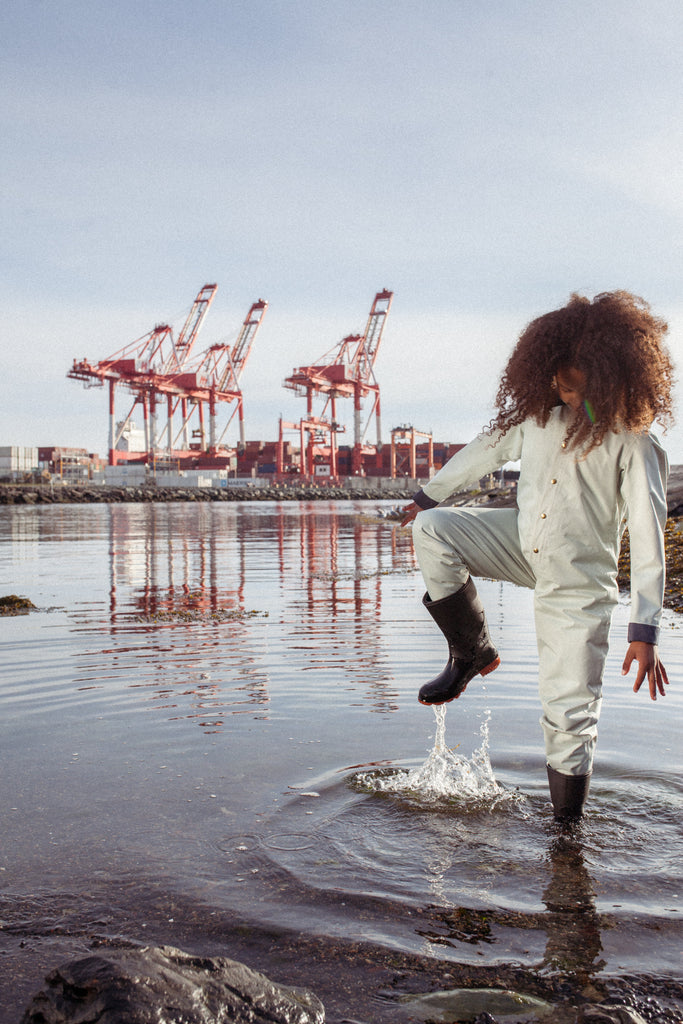Little girl wearing her Fair Child 100% waterproof children's coverall and playing in the water.