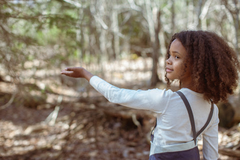 Child extending their arm in a wooded landscape.