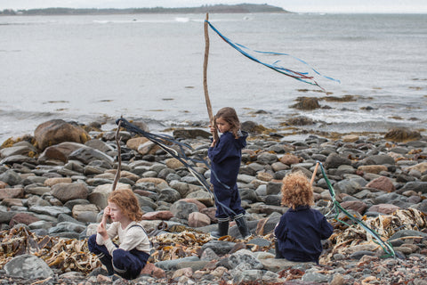 Children playing on beach in their Faire Child Weather Wear Sustainable Clothing.