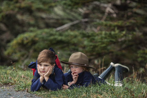 Children wearing Faire Child's Eco friendly outdoor clothing playing in the woods.