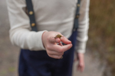 Child holding a snail while in class at the ever green club forrest school.