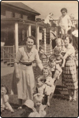 Image of the Mcmillian sisters with their students at the open-air nursery.
