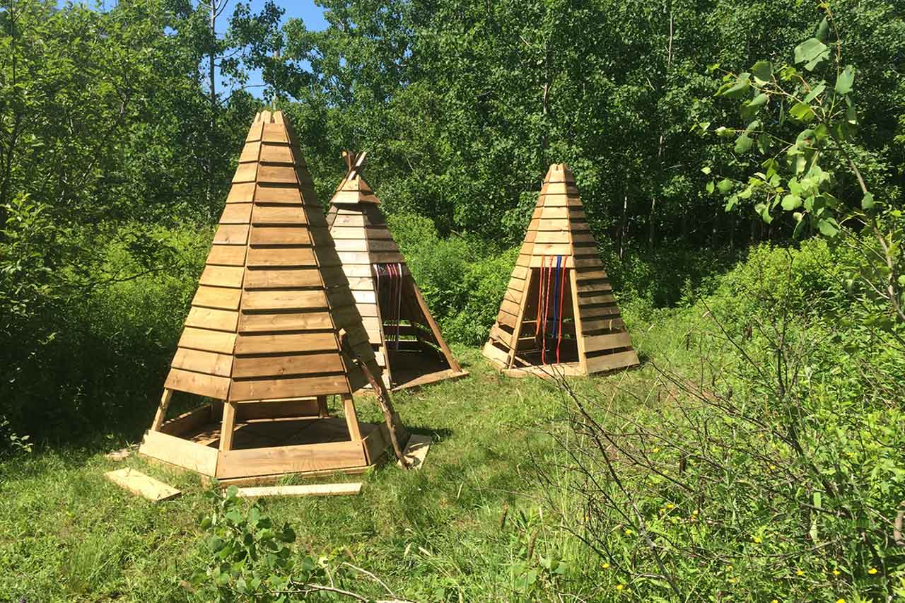 Three wooden play huts constructed outside.