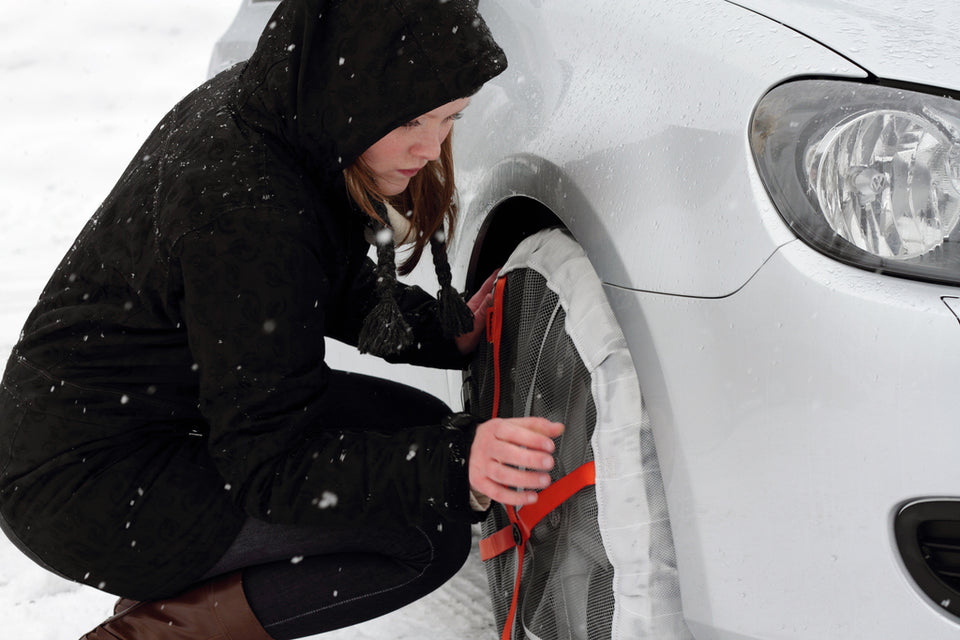 Woman installs AutoSock on the front wheel of a car