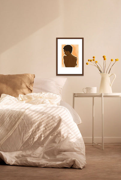 A bedroom wall with hung and framed sensual artwork of a black woman with natural hair's nude back