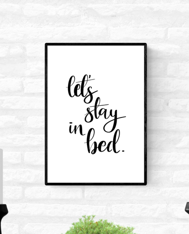 "Wall quote print in a thin black frame with the words, ""Let's stay in bed"""